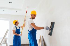 Deux artisans peignent un mur