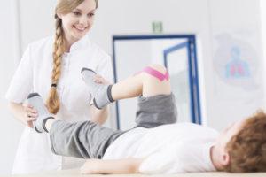 Jeune kinésithérapeute au travail soignant un enfant